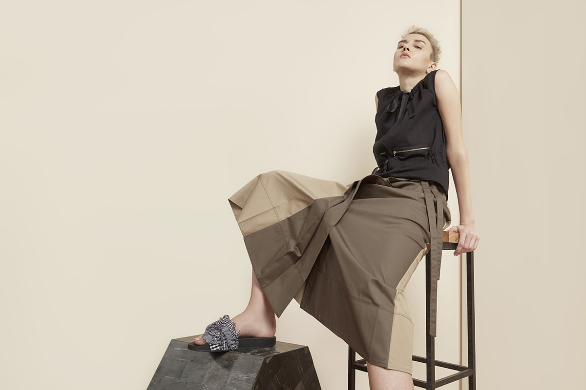 Fashion model poses in skirt and shirt leaning back on a high stool