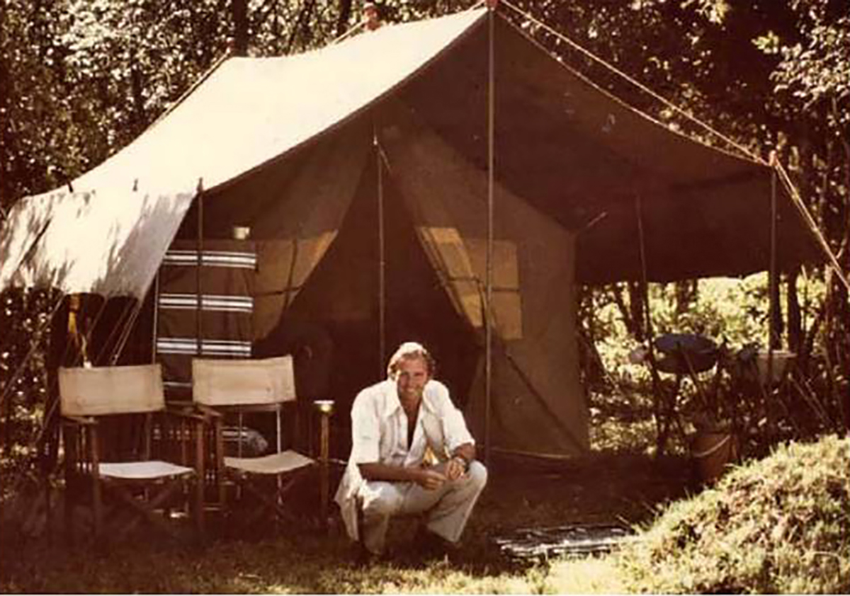 Abercrombie and Kent founder Geoffrey Kent poses crouching in front of luxury safari tent in Tanzania