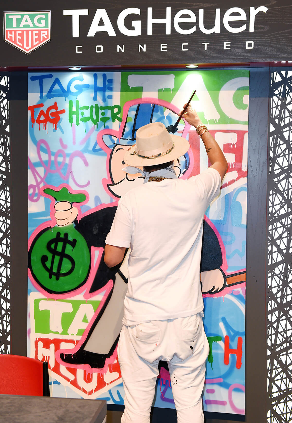 Street artist Alec Monopoly painting TAG Heuer onto wall