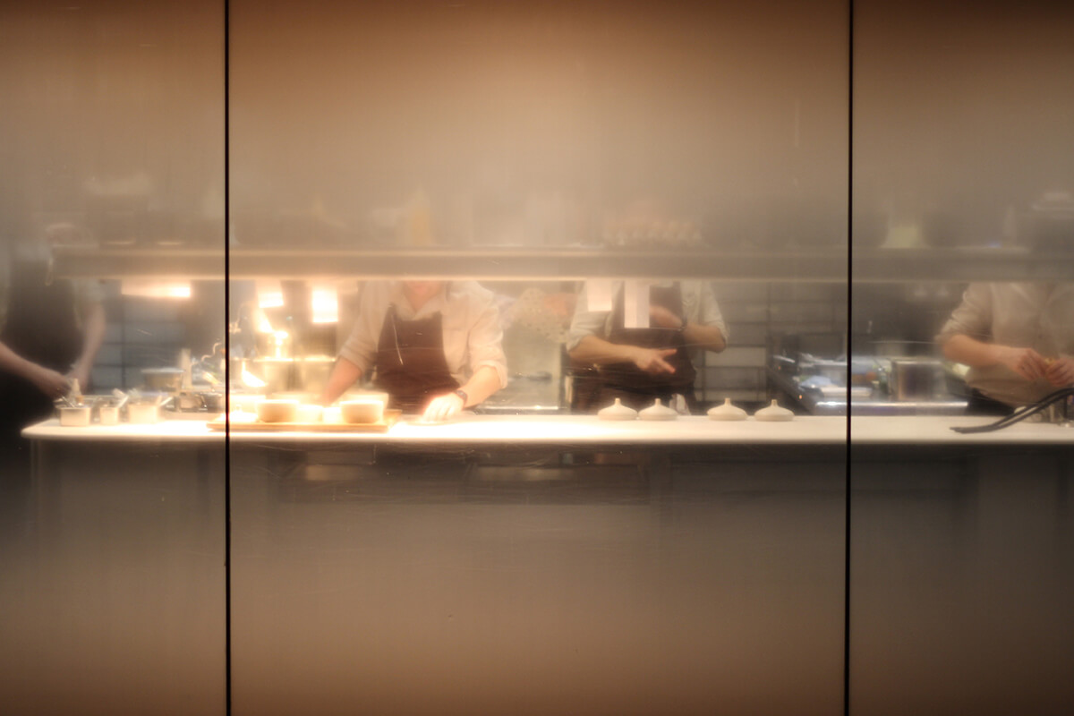 Open restaurant kitchen with window showing chefs preparing food