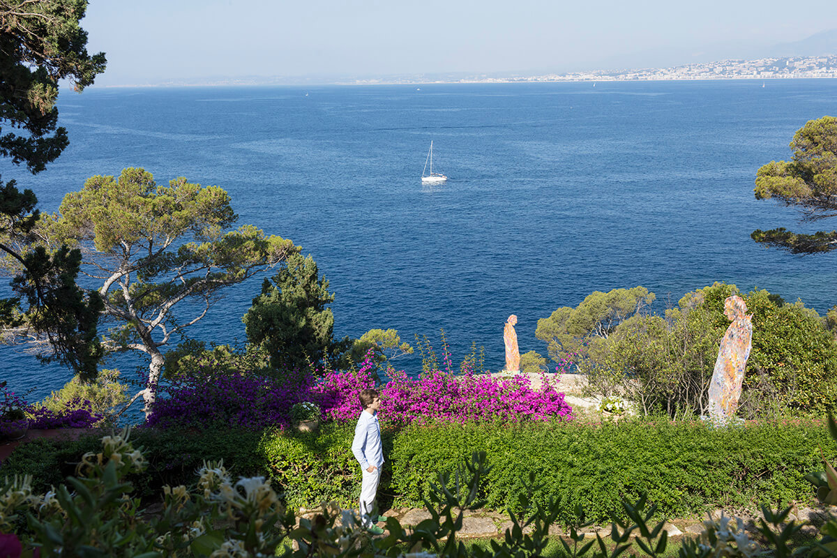 Artist Sassan Behnam-Bakhtiar standing in garden with his sculptures and the ocean in the distance