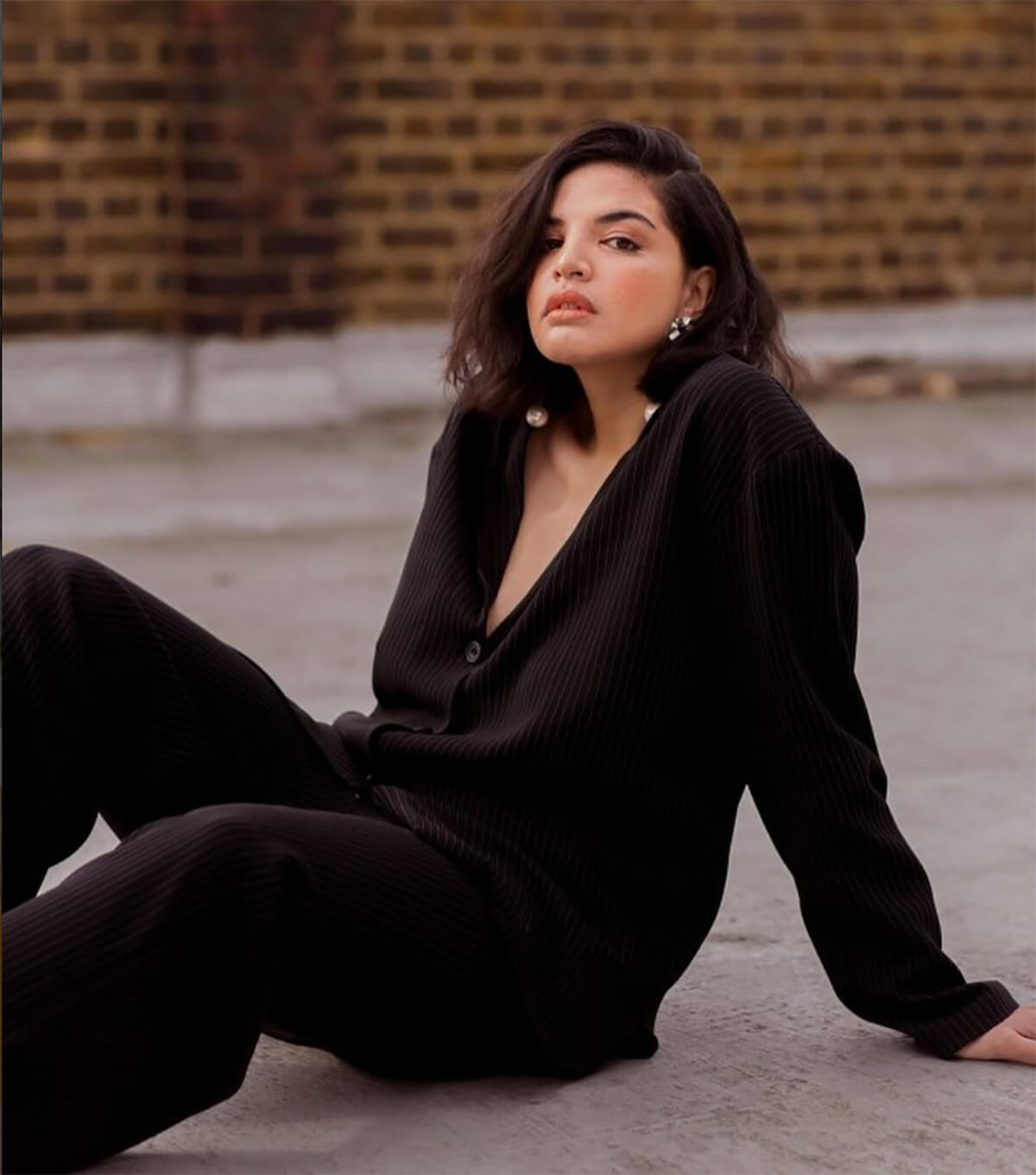 Model wearing black jumpsuit reclining on the ground