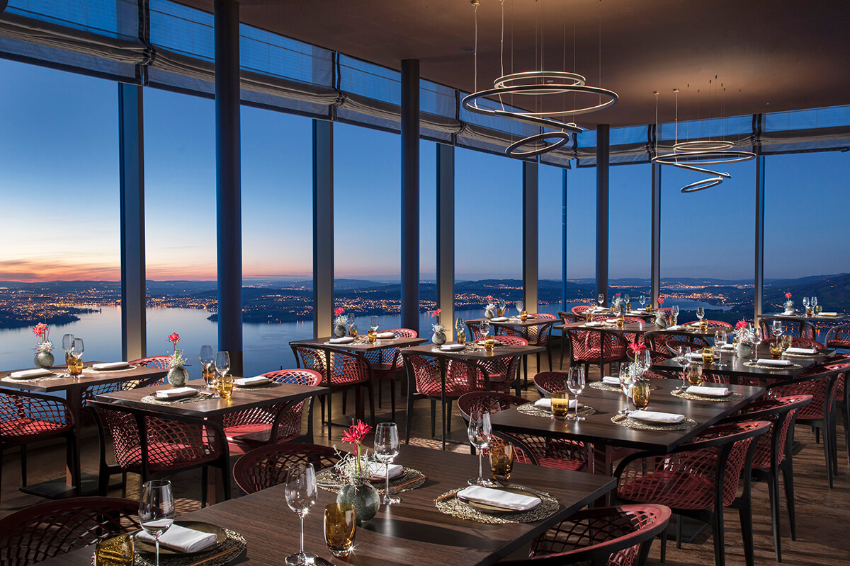 Luxury restaurant dining room with large glass windows providing views of a lake