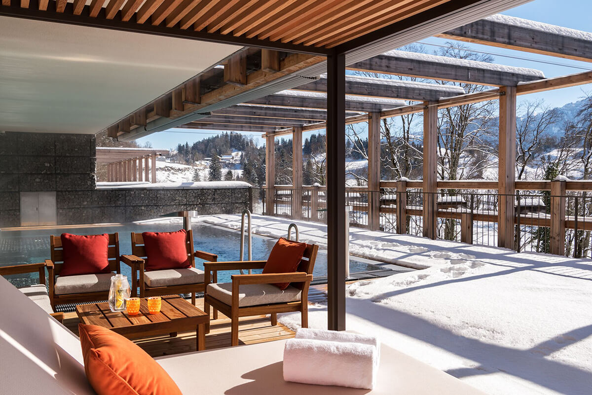 outdoor pool surrounded by snow with steam rising and plush surrounding sun loungers