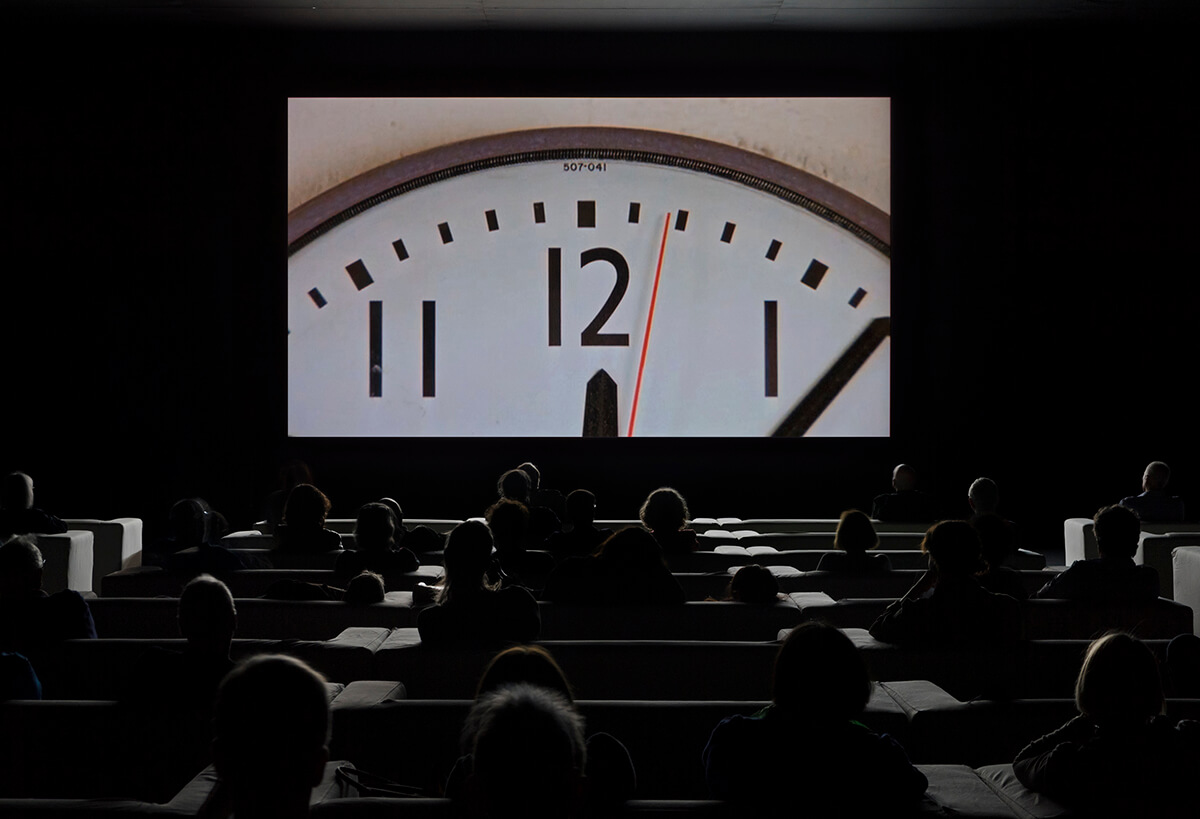Cinema with a screen showing the top of a clock with people sitting in rows of seats