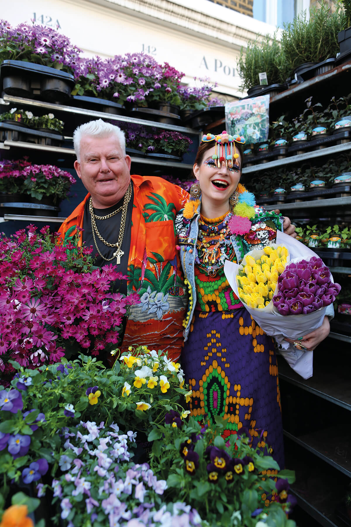 Designer Anne Sophie Cochevelou pictured in flower market holding a bunch of colourful flowers