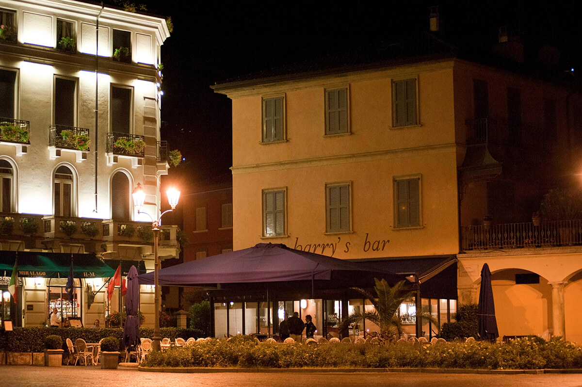 Image of traditional Italian restaurant at night with tables underneath a mauve awning