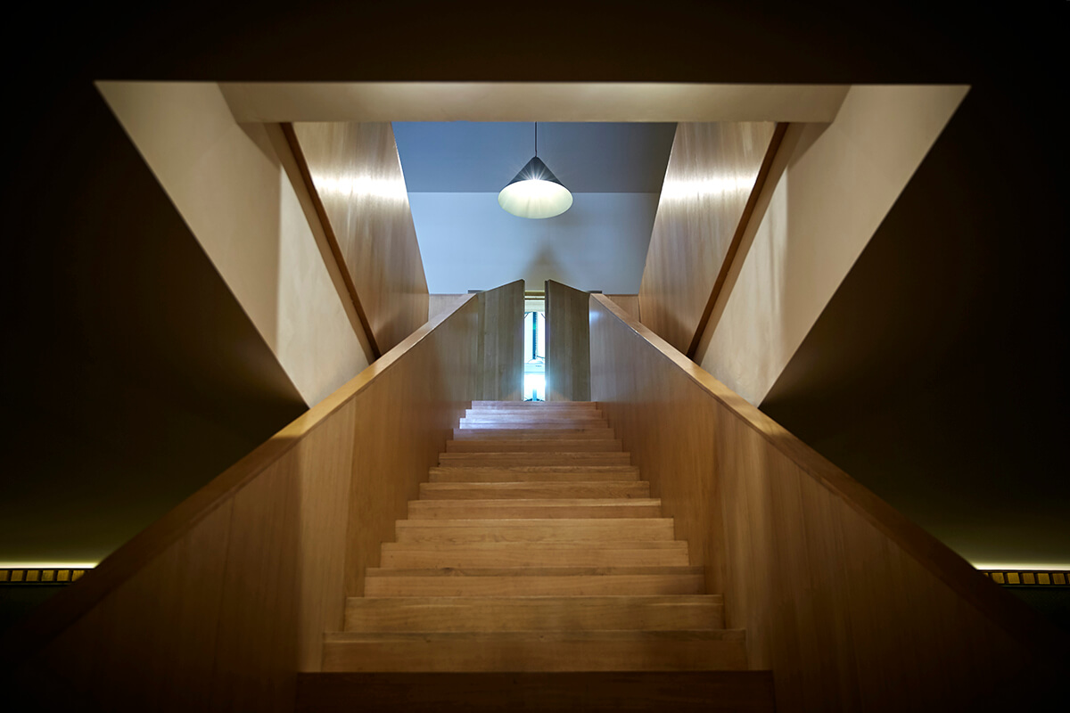 Architectural photograph of stairway leading up to a landing with a hanging light