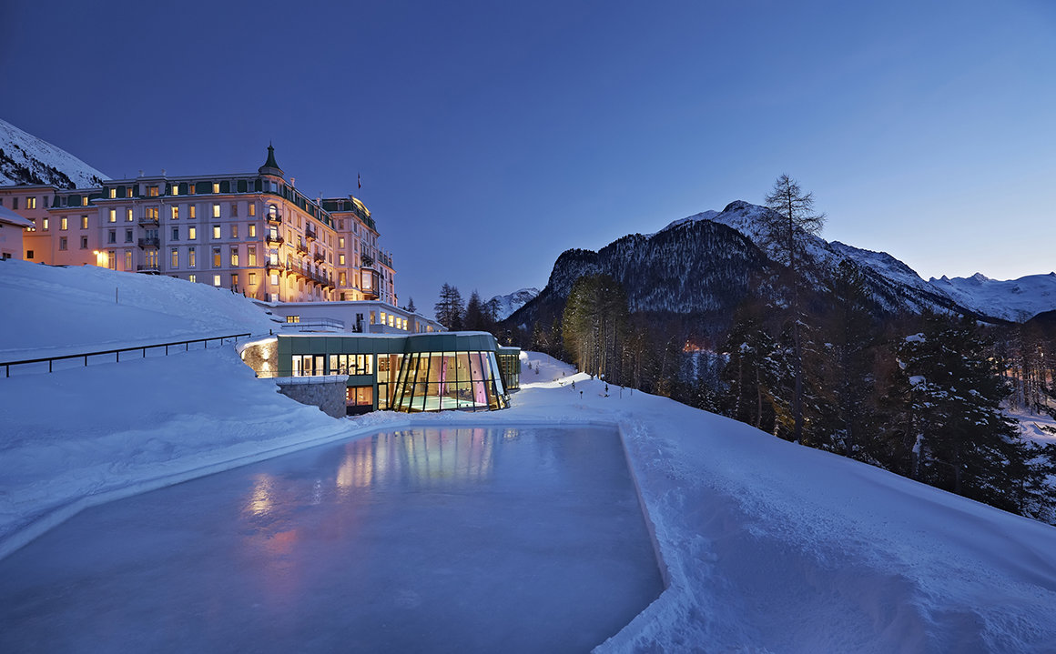Ski resort hotel pictured at night with an indoor swimming pool and ice rink