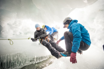 Explorers climb through an ice cave in the South Pole