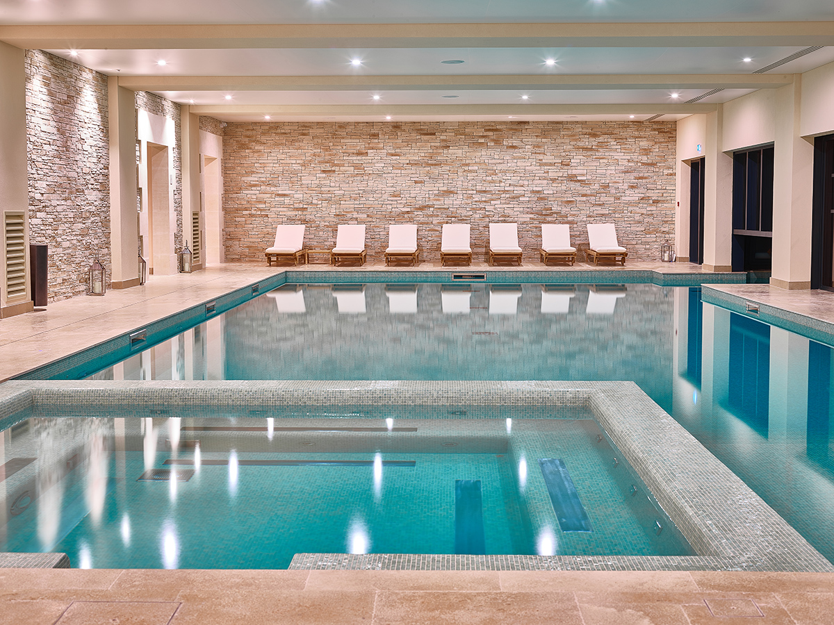 Luxury spa swimming pool with sun loungers