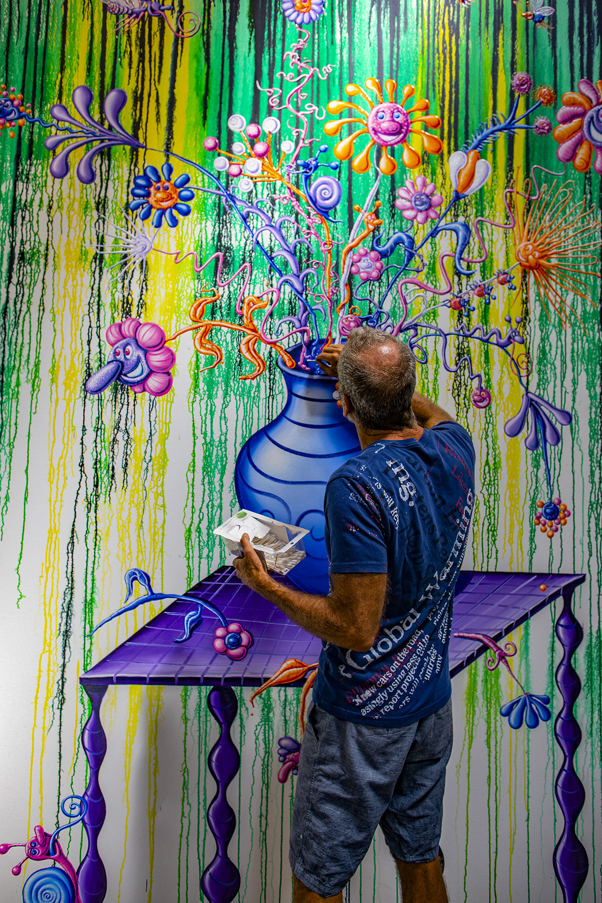 Artist Kenny Scharf painting an abstract composition of flowers