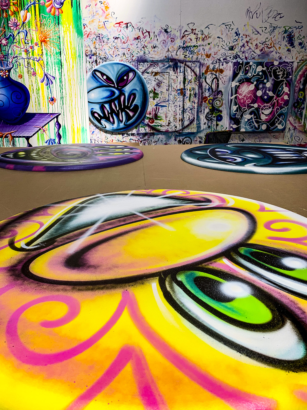 Kenny Scharf round paintings in his studio
