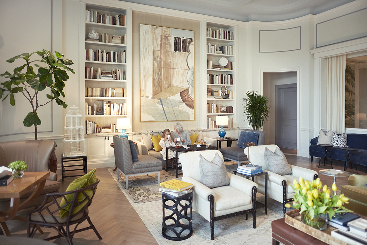 Luxury interiors of a large sitting room area with people drinking tea on the sofa