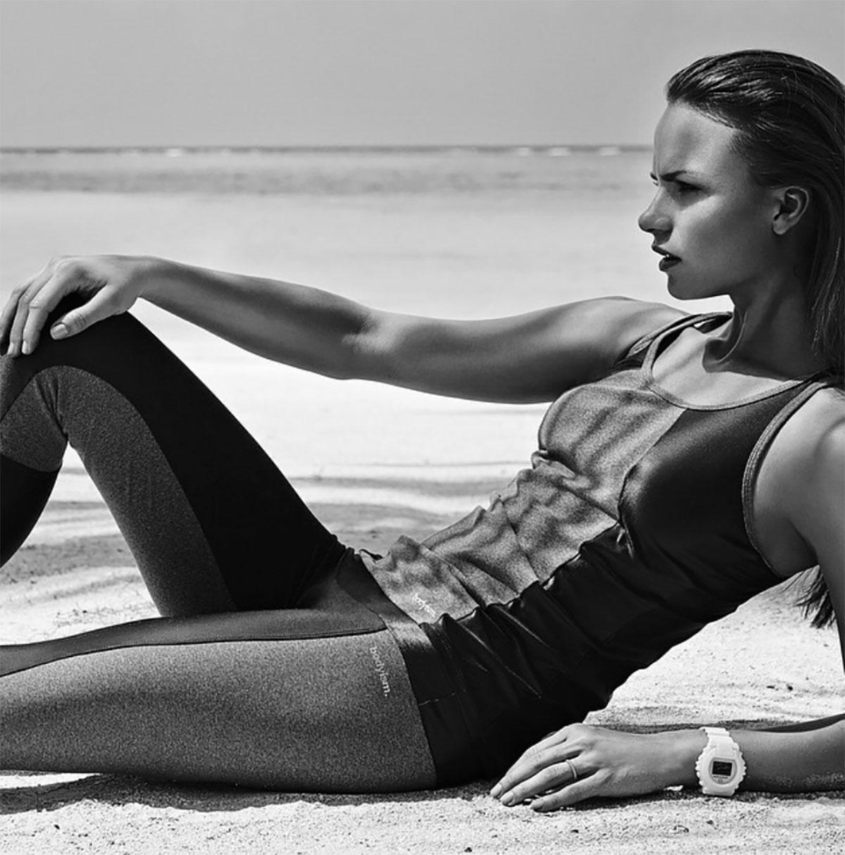 Model lying on a beach in sportswear