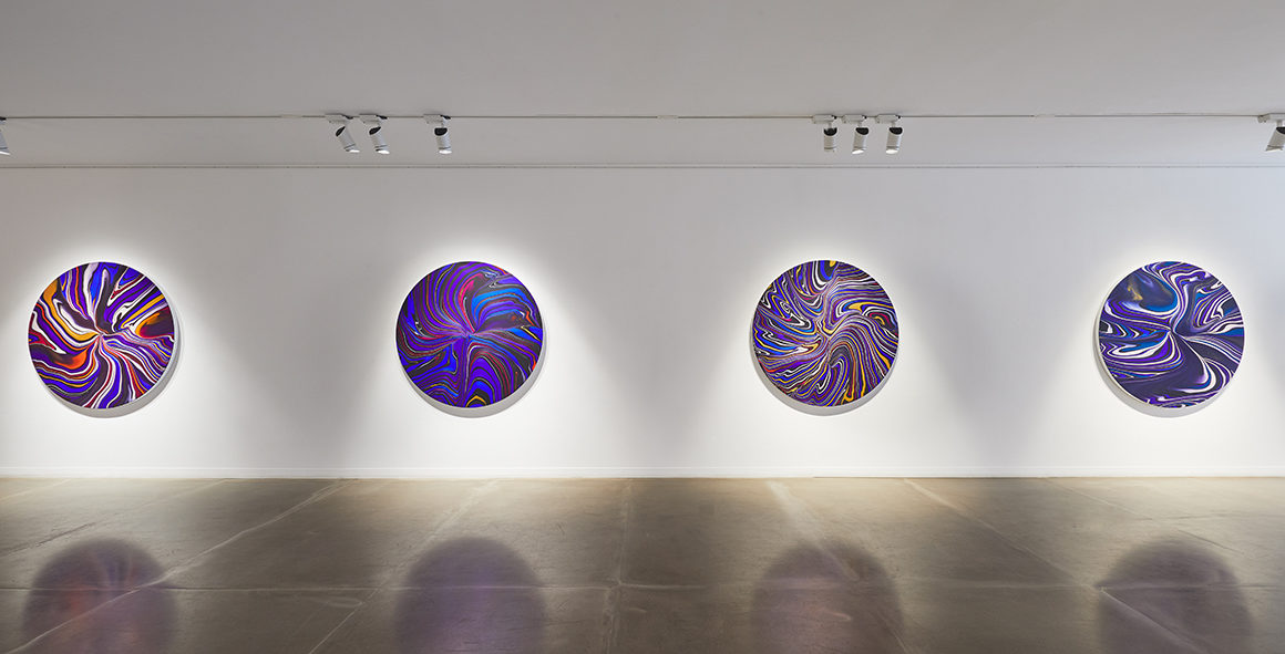 Installation view of a contemporary art exhibition with round canvases