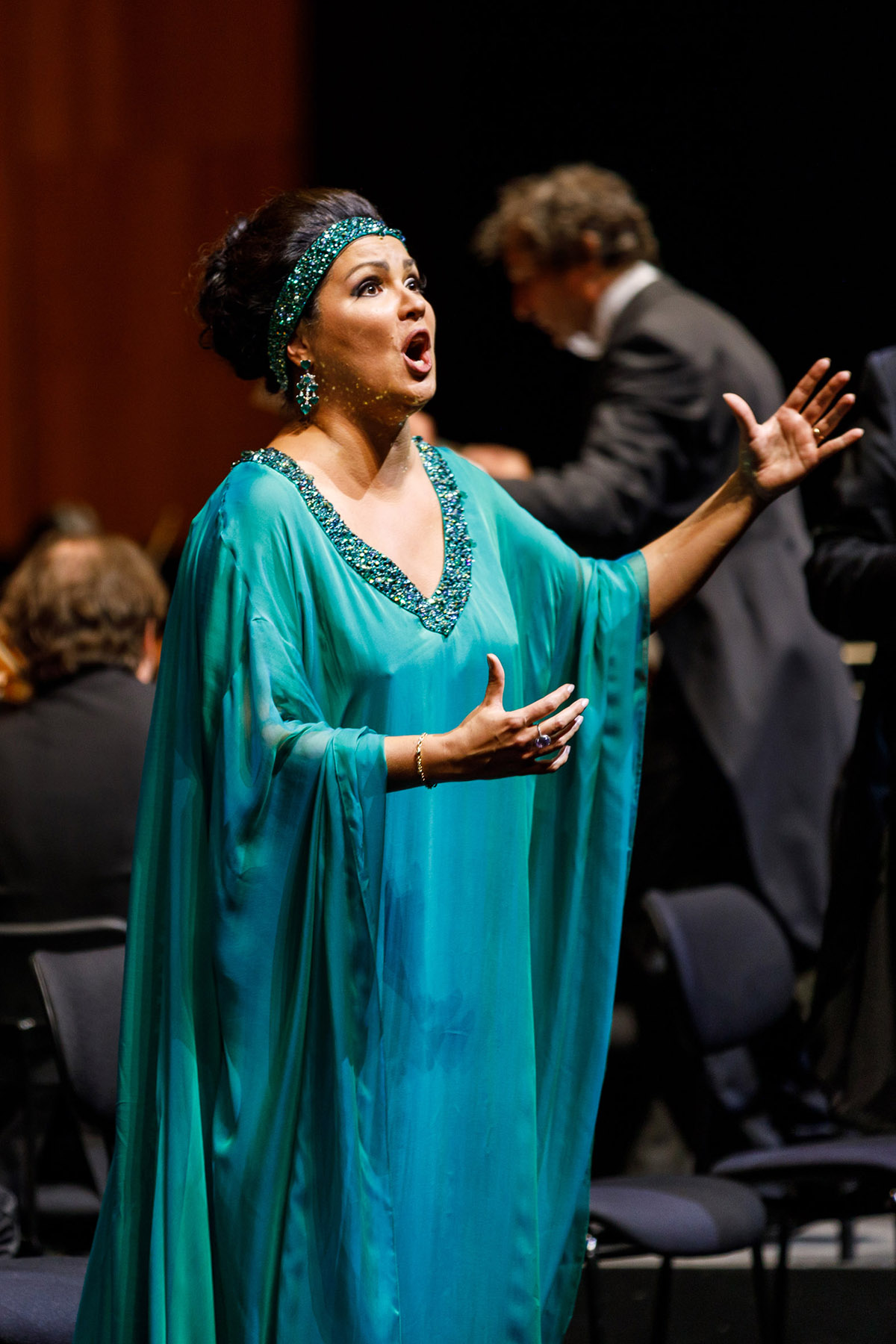 Female opera singer mid performance in a blue Arabian style dress