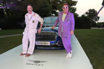 Sir Elton John standing with a Bentley sports car