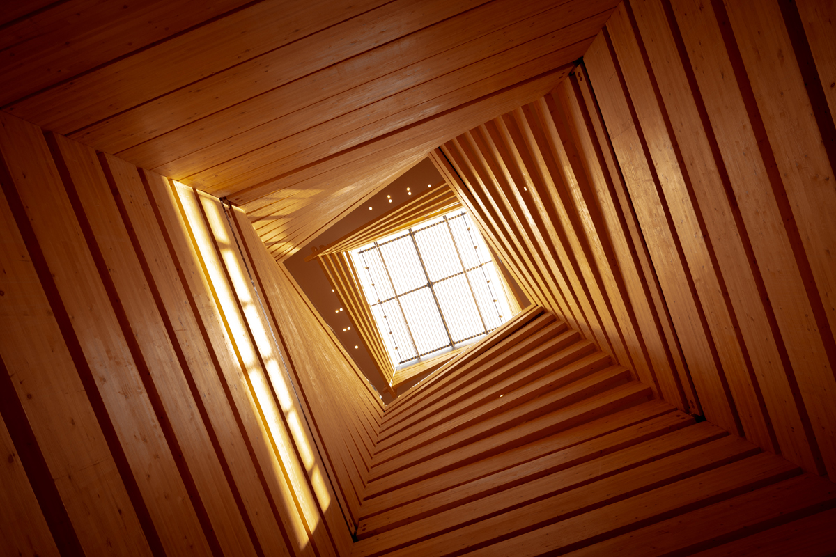 Contemporary light well inside a building made from wooden panels