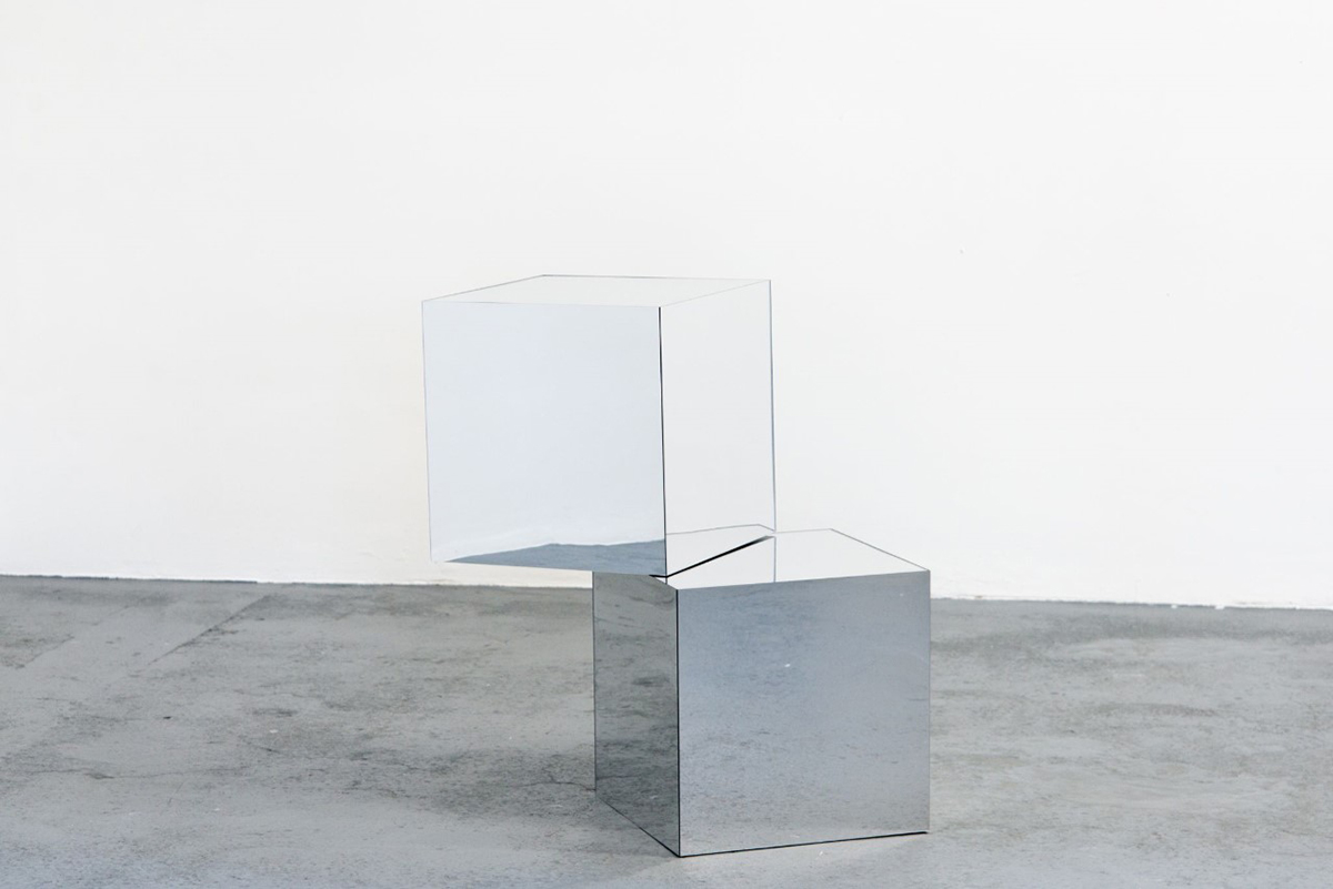 Two reflective boxes stacked on top of each other in a white room