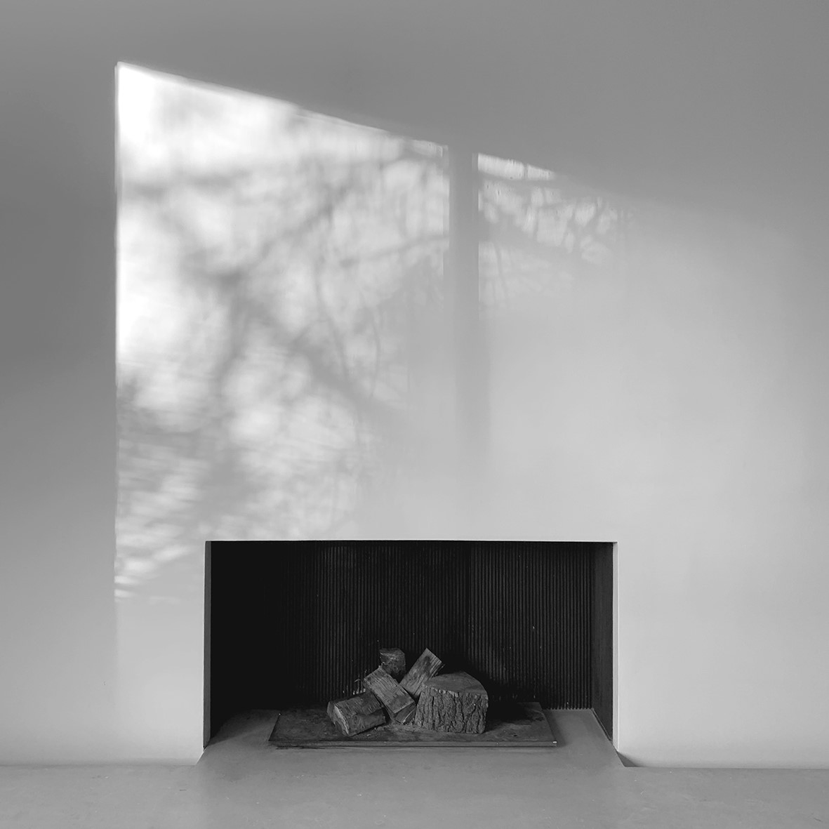 Fire place photographed in black and white with light and shadow on wall
