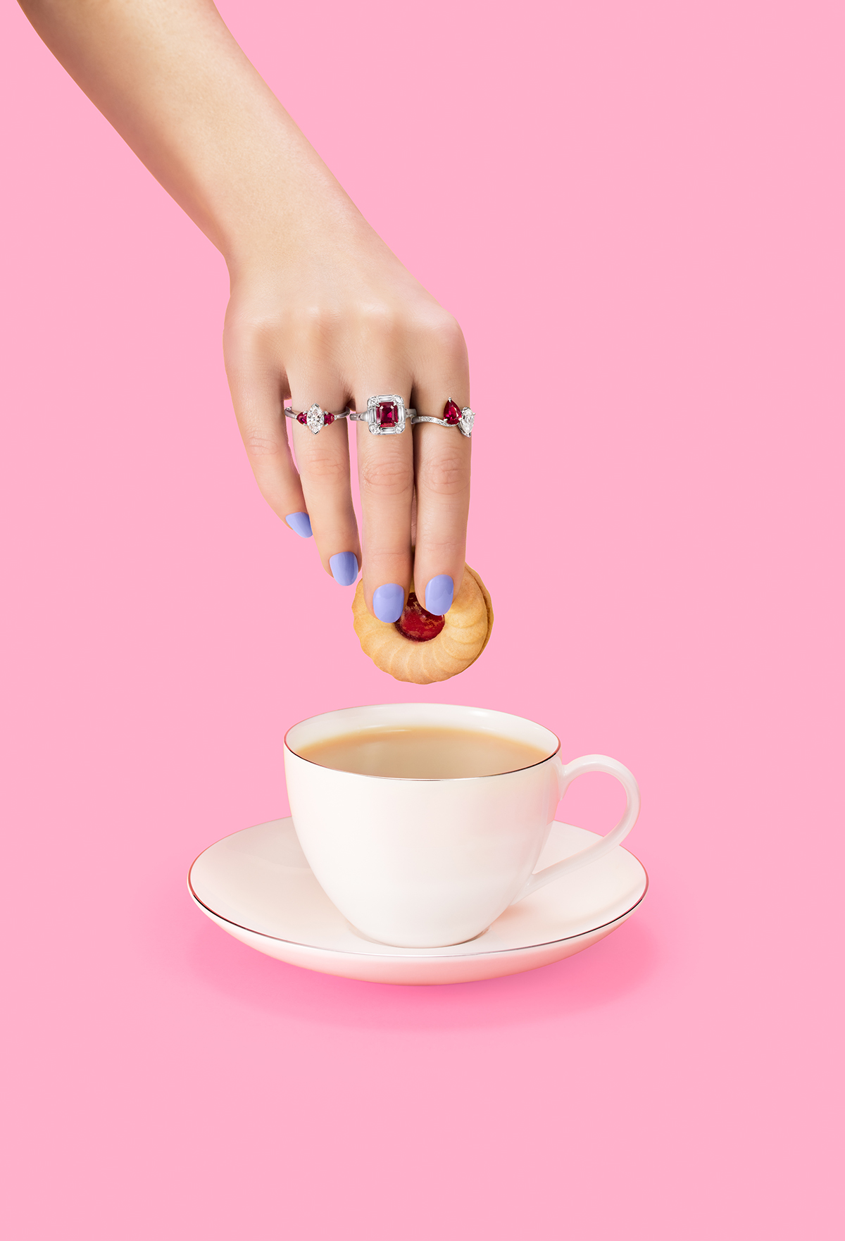 rings on a woman's hand shown dipping biscuit into tea