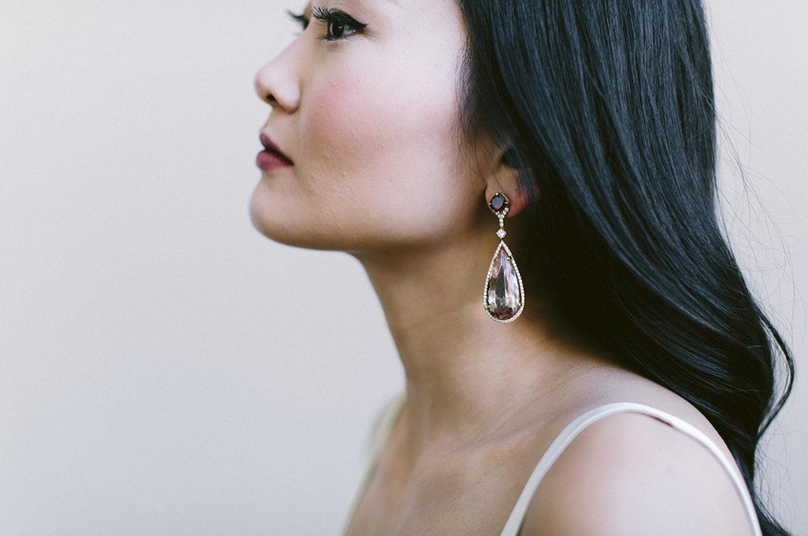 Model wearing drop earrings